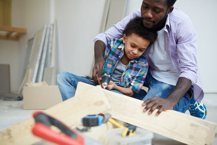 Dad and son drilling hole into piece of wood