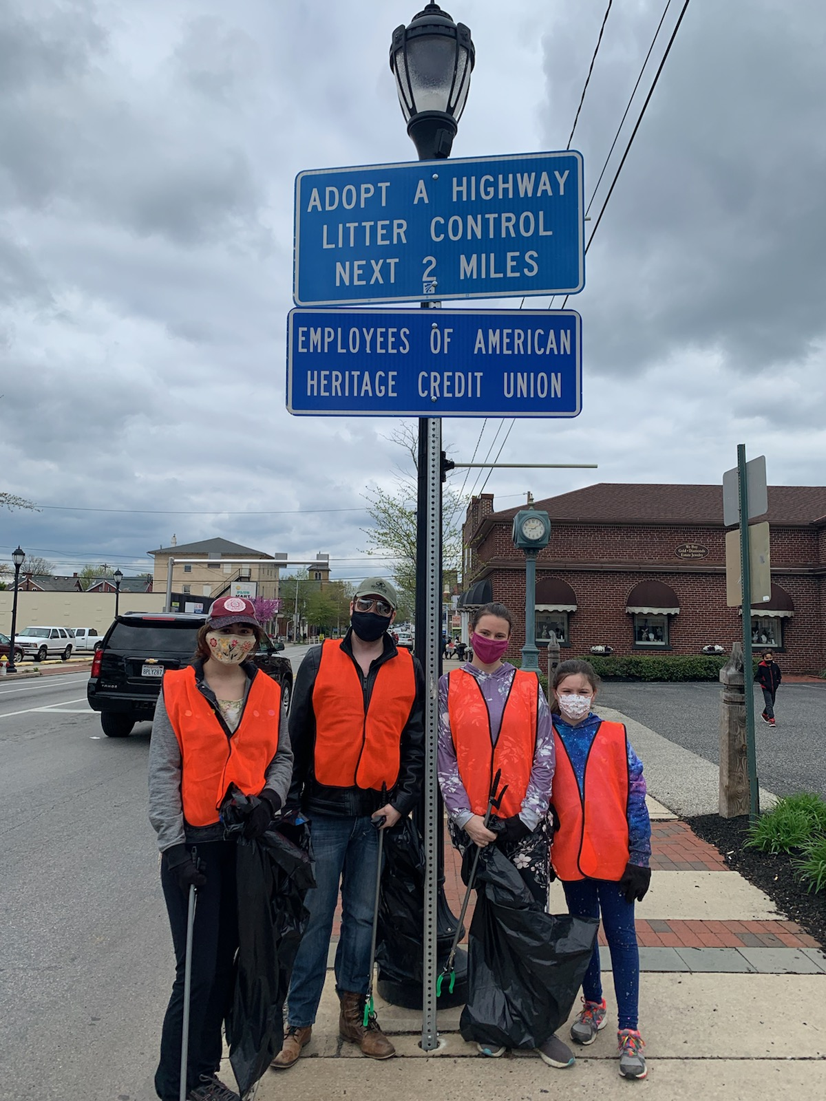 Volunteers stand under an Adopt-A-Highway sign for clean-up event.