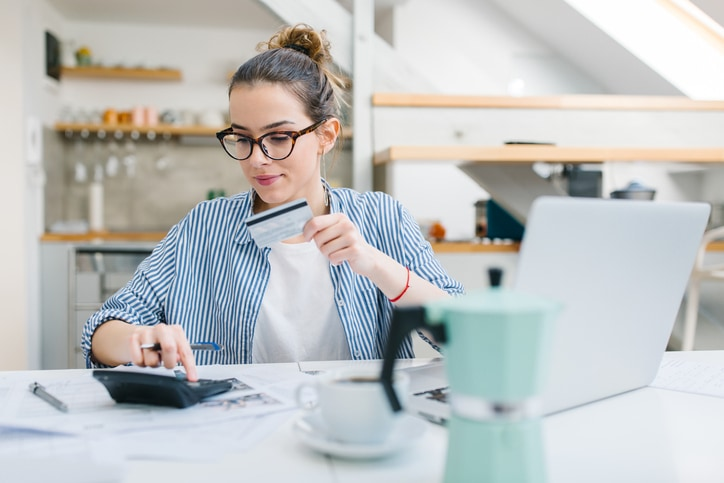 Woman planning out budget with card and computer